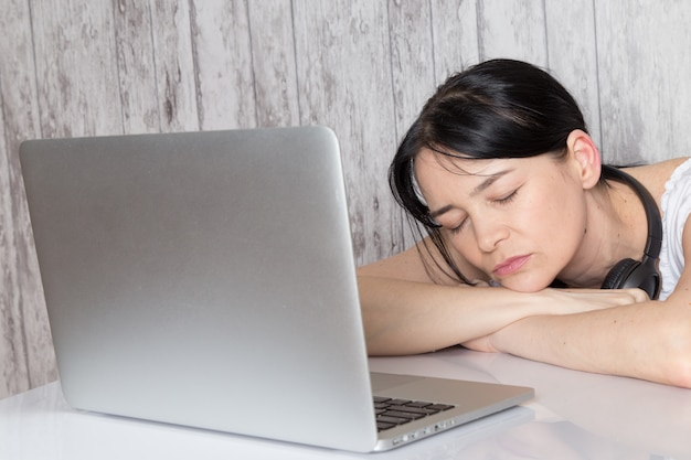 Young lady in white shirt with black earphoens fell asleep in front of laptop on grey