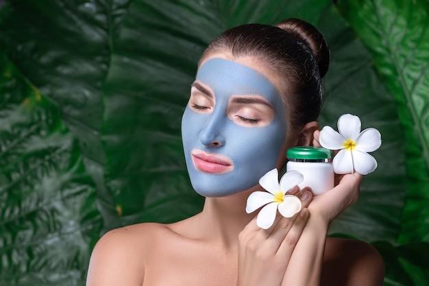 彼女の顔に青い粘土マスクを持つ若い女性。若い女性がプルメリアの花を持っています。スパ
