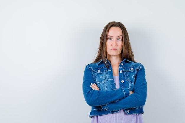 Tシャツ、ジャケットで腕を組んで真面目な顔つきの若い女性、正面図。