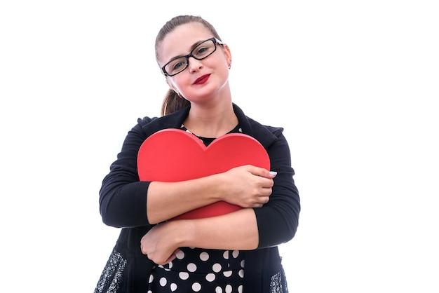 白で隔離される大きな赤いハートを持つ若い女性