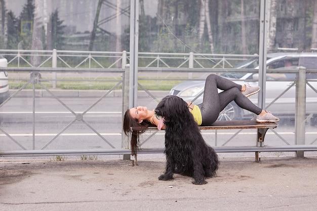 그녀 근처에 검은 briard와 젊은 아가씨는 버스를 기다리는 동안 대중 교통 역의 벤치에 누워 있습니다.