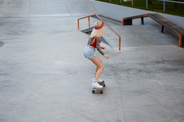 Young lady with blonde hair, with tattooed arms, wears in a red t-shirt and denim shorts, with a knitted bandana on her head, enjoying longboarding in skate park.