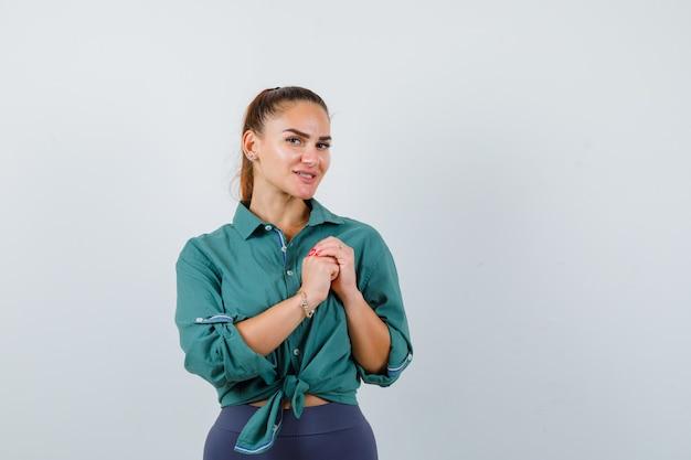 緑のシャツを着て胸に手を握りしめ、陽気に見える若い女性、正面図。