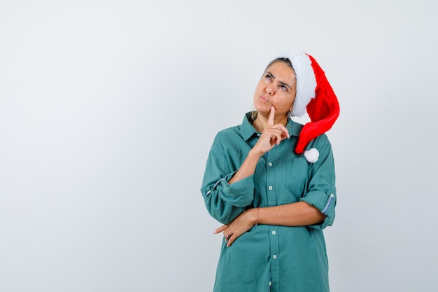 Giovane signora con il dito sul mento in cappello di natale, camicia e sguardo pensieroso, vista frontale.