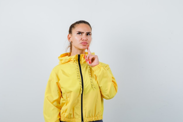 Young lady with finger on chin in yellow jacket and looking pensive , front view.