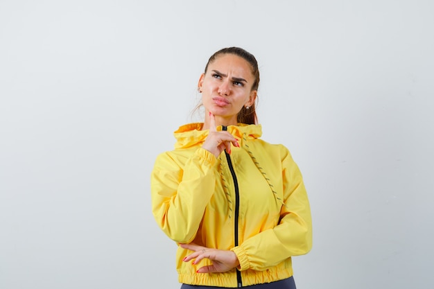 Young lady with finger on chin in yellow jacket and looking thoughtful. front view.