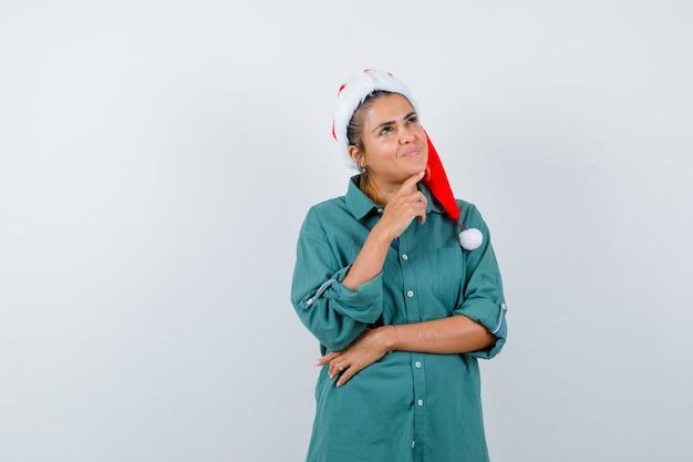 クリスマスの帽子、シャツ、喜んで見えるあごの下に指を持つ若い女性。正面図。