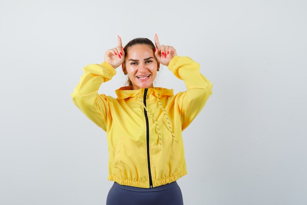 Young lady with fingers over head as bull horns in yellow jacket and looking funny. front view.