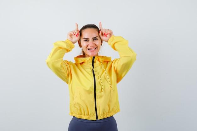 黄色いジャケットの雄牛の角のように頭の上に指を持ち、おかしな顔をしている若い女性。正面図。