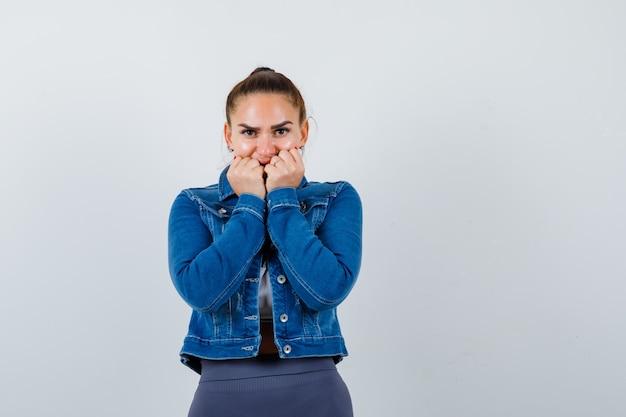 Giovane donna con i pugni sulla bocca in alto, giacca di jeans e dall'aspetto fiducioso. vista frontale.