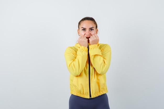 Девушка с кулаками возле рта в желтой куртке и озадаченный вид, вид спереди.