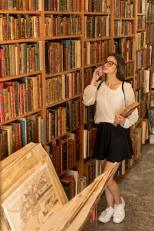 Young lady with glasses talking on phone and holding book
