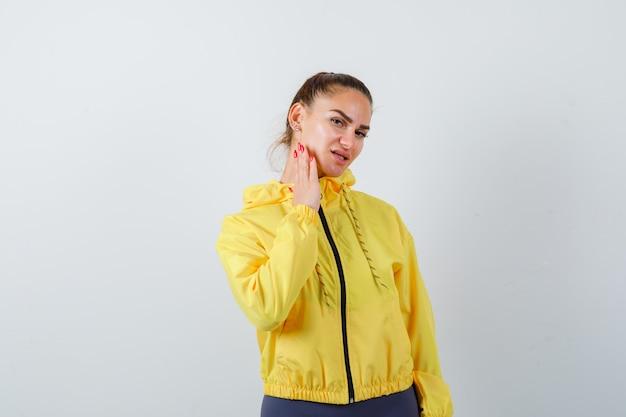 Giovane donna con la mano sulla guancia in giacca gialla e guardando attenta, vista frontale.