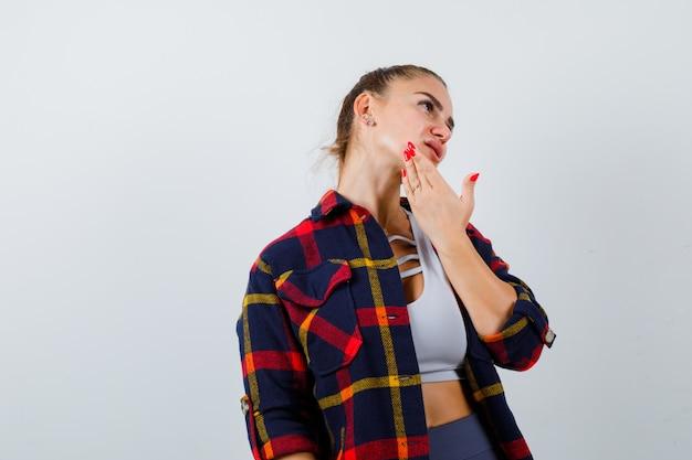 Giovane donna con la mano sul mento in alto, camicia a quadri e sguardo pensieroso. vista frontale.