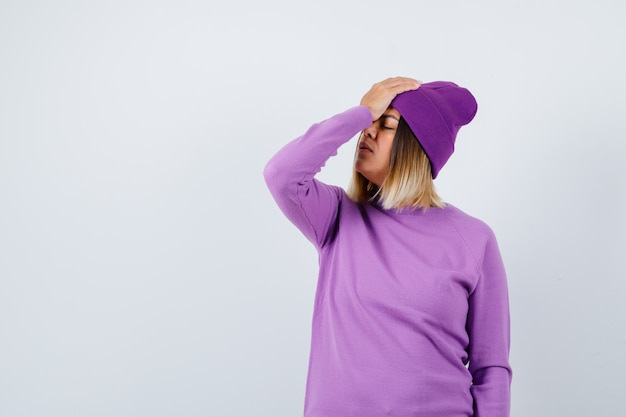 Young lady with hand on forehead in purple sweater, beanie and looking tired. front view.