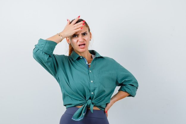 Giovane donna con la mano sulla testa in camicia, pantaloni e aspetto turbato, vista frontale.