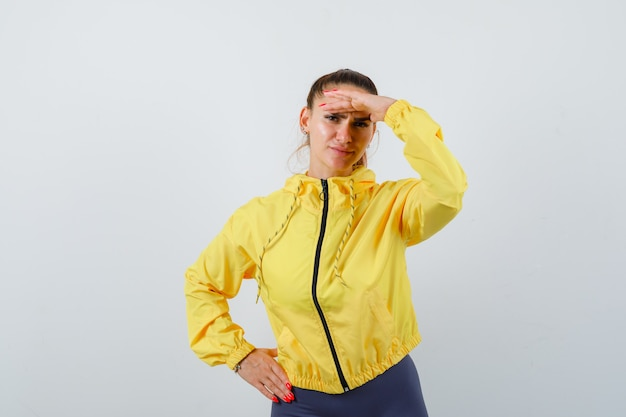 Young lady with hand over head in yellow jacket and looking thoughtful. front view.