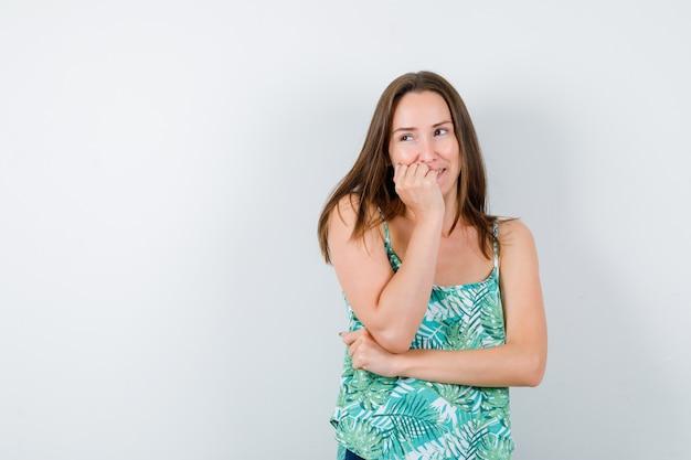 Молодая дама с рукой на щеке в блузке и выглядит мило. передний план.