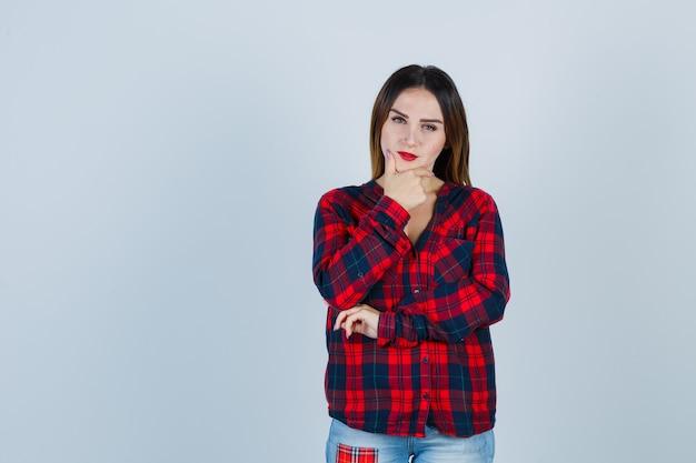 チェックのシャツを着て、あごに手を置いて、インテリジェントに見える若い女性。正面図。