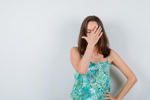 顔に手を持って、イライラしている、正面図を探している若い女性。