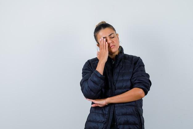 ダウンジャケットを着て、疲れているように見える顔に手を持っている若い女性。正面図。