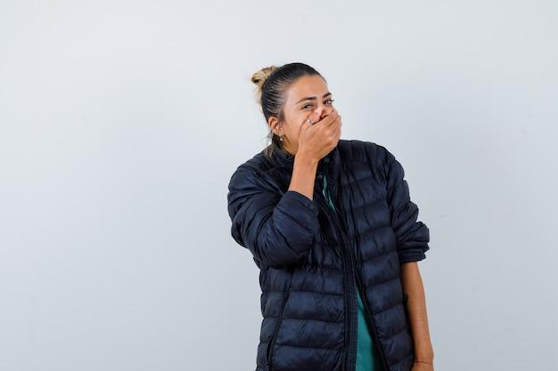 ダウンジャケットを着て口に手を当てて、うれしそうに見える若い女性、正面図。 無料写真