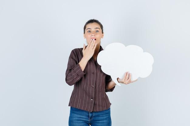 口に手を持っている若い女性、シャツ、ジーンズで紙のポスターを保持し、驚いて見える、正面図。