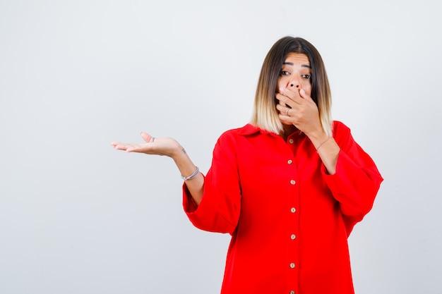 赤い特大のシャツで何かを見せて、困惑しているように見える間、口に手を持っている若い女性、正面図。