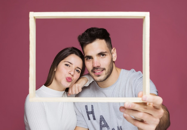 Young lady with hand on shoulder of positive guy holding photo frame