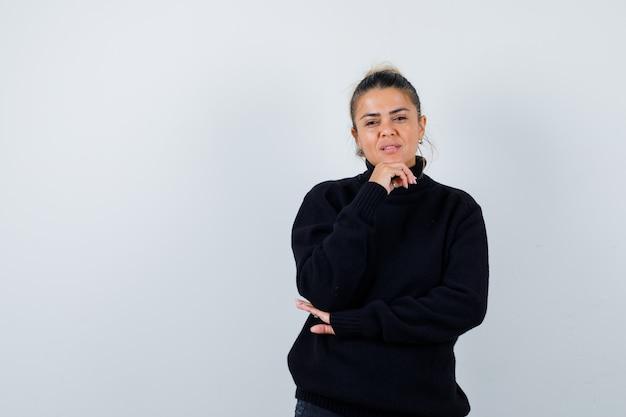 黒のセーターで顎の下に手を持って、思慮深く見える若い女性。正面図。