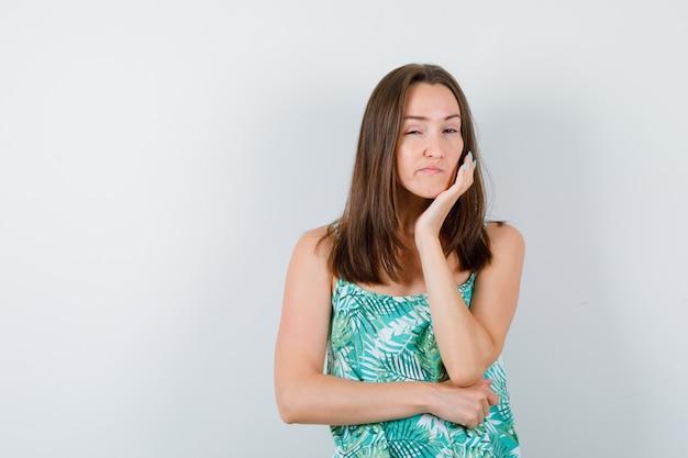 Молодая дама с рукой под подбородком в блузке и задумчивым взглядом, вид спереди.