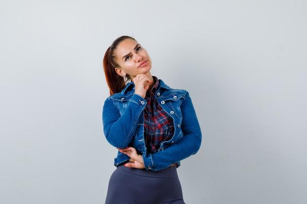 市松模様のシャツ、デニムジャケット、物思いにふけるあごの下に手を持つ若い女性。正面図。