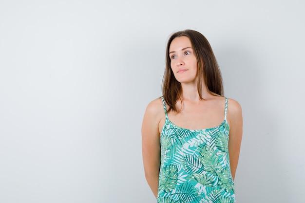 目をそらし、思慮深く見ながら後ろ手で若い女性。正面図。