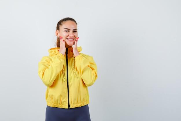Giovane donna con le mani sulle guance in giacca gialla e sembra felice. vista frontale.
