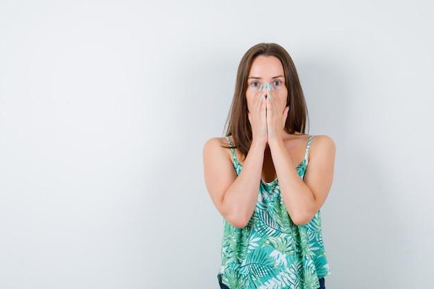 Giovane donna con le mani sul viso e dall'aspetto ansioso. vista frontale.