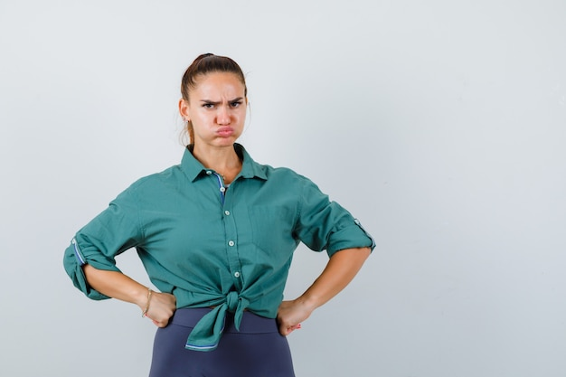Young lady with hands on hips, blowing cheeks in green shirt and looking angry , front view.
