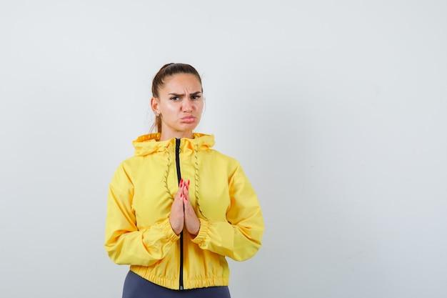 黄色のジャケットでジェスチャーを祈り、希望を持って見える手を持つ若い女性。正面図。