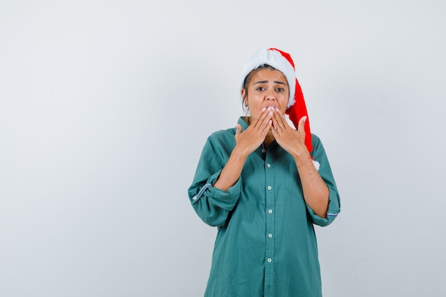Giovane donna con le mani sulla bocca in cappello di natale, camicia e sembra spaventata. vista frontale.