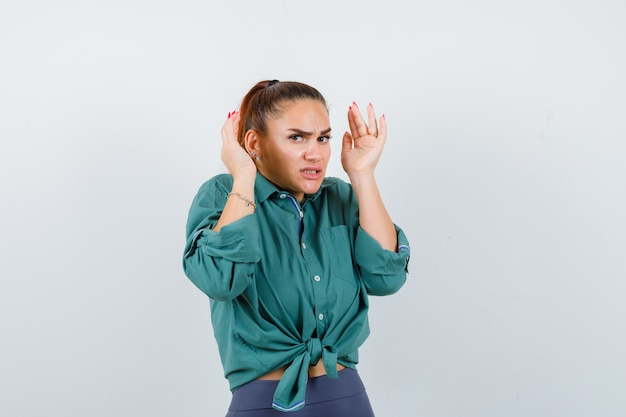 Young lady with hands near head in shirt, pants and looking anxious , front view.