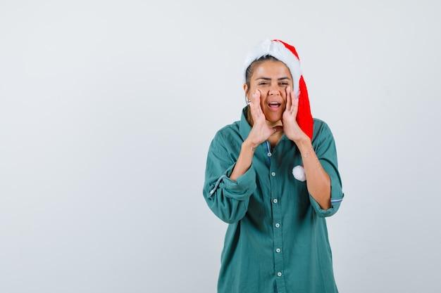 クリスマスの帽子、シャツ、陽気に見える、正面図で秘密を伝えるために口の近くに手を持っている若い女性。