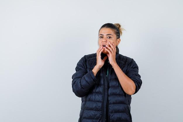 ダウンジャケットの開いた口の近くに手を持って、驚いたように見える若い女性、正面図。