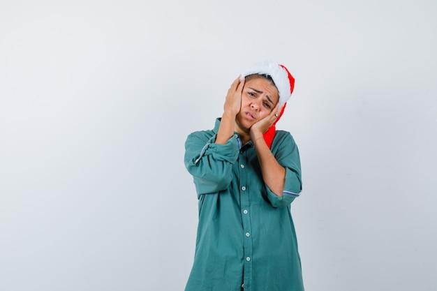 クリスマスの帽子、シャツ、失望した、正面図で頬に手を持っている若い女性。