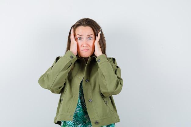 緑のジャケットを着て頬に手を当てて、興奮しているように見える若い女性、正面図。