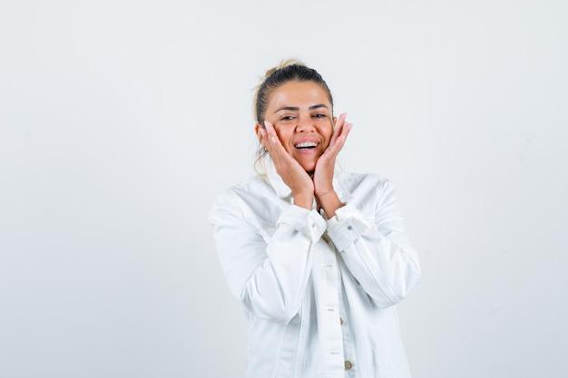 Молодая дама с руками на щеках в рубашке, белой куртке и радостным взглядом. передний план.