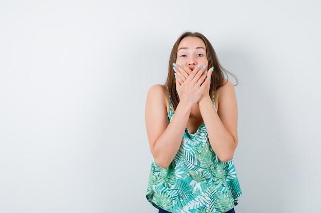 口に手を当てて驚いて見える若い女性。正面図。