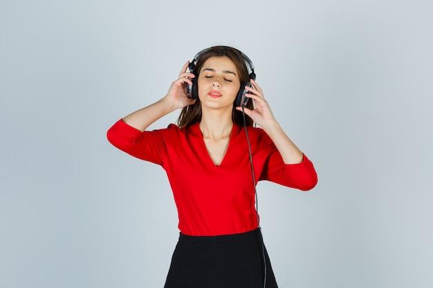 Молодая дама с наушниками в красной блузке, юбке слушает музыку и выглядит счастливой