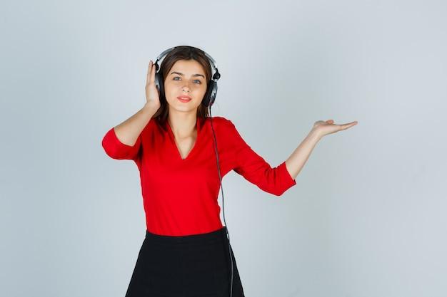 Giovane signora con le cuffie che ascolta la musica mentre mostra qualcosa in camicetta rossa