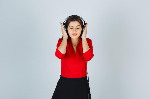 Молодая дама в наушниках слушает музыку в красной блузке, юбке и выглядит довольной