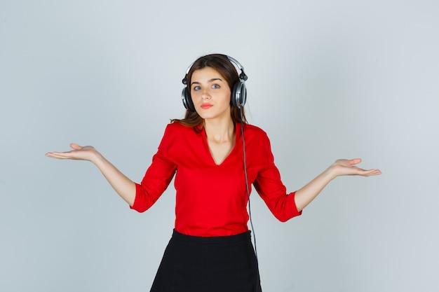 Молодая дама в наушниках слушает музыку, делая жест весов в красной блузке