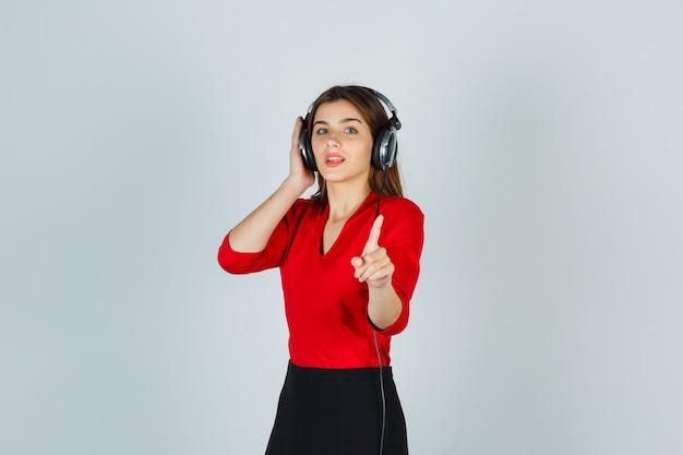 Giovane donna con le cuffie in camicetta rossa, gonna che ascolta la musica mentre indica lontano